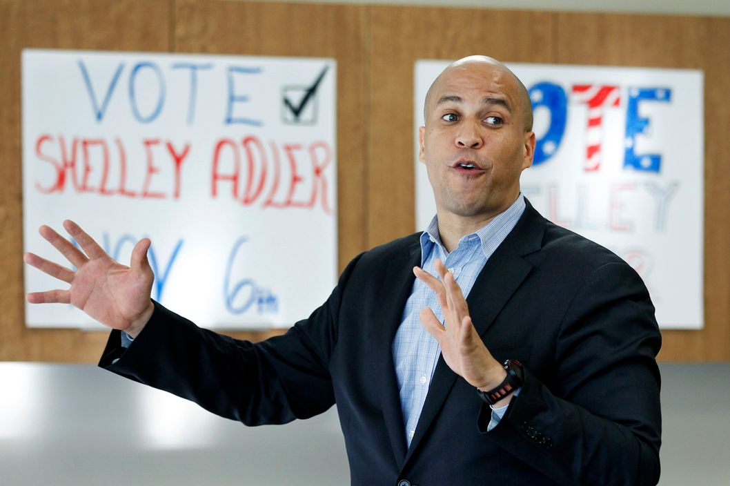 In this Wednesday, Oct. 10, 2012 photograph, Newark Mayor Cory Booker, center, addresses a gathering at a campaign event for Shelley Adler in Willingboro Township, N.J. Adler is challenging incumbent, former Philadelphia Eagles football star, Republican Rep. Jon Runyan in the 3rd Congressional District. New Jersey's most recognizable politicians, Democrat Booker and Republican Gov. Chris Christie, are buttressing their national profile this election season, stumping for candidates eager to cash in on their growing popularity and name recognition while simultaneously earning their own political chits. The two men say they are being party loyalists and answering calls to help elect their chosen candidates. (AP Photo/Mel Evans)