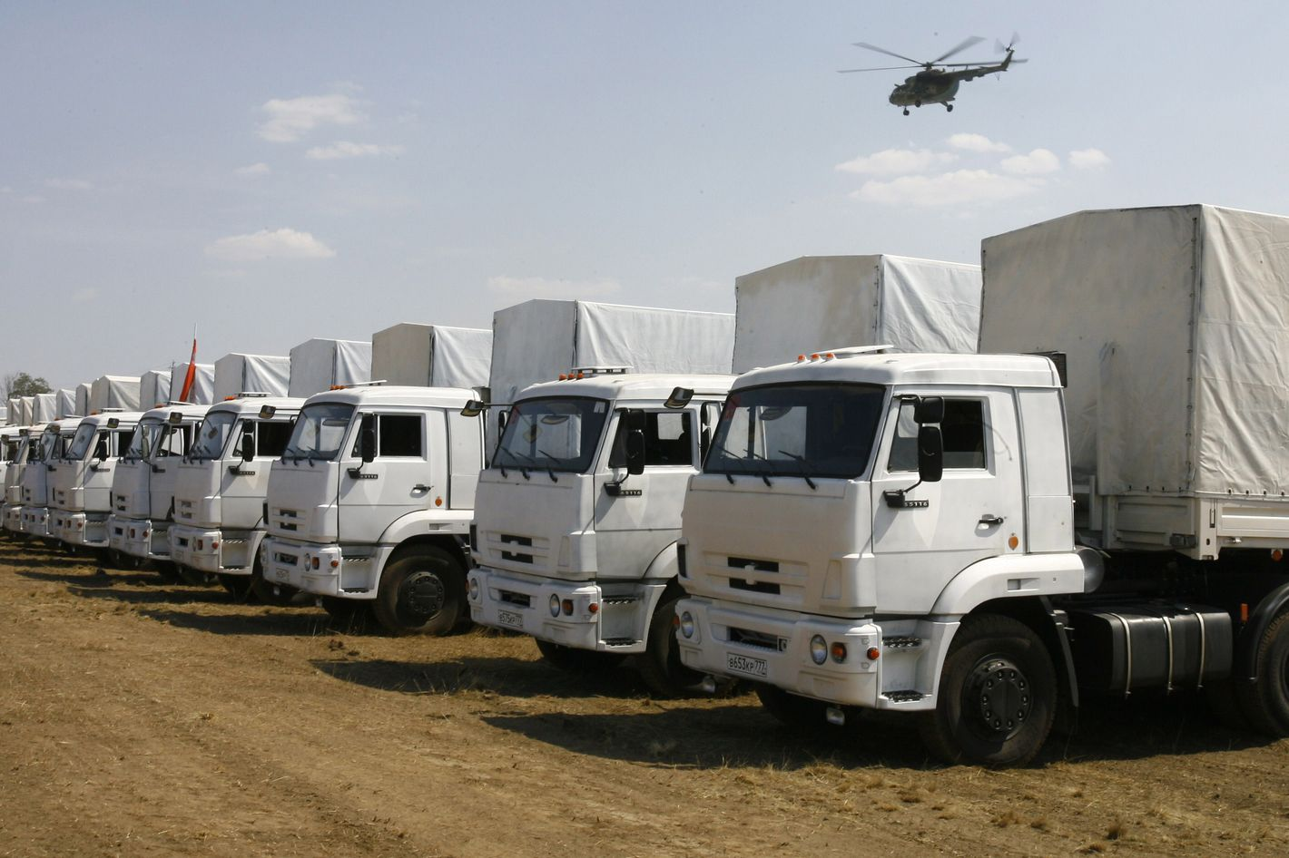 "Trucks from a Russian humanitarian convoy are parked on a field outside the town of Kamensk-Shakhtinsky in the Rostov region, some 30kms from the Russian-Ukrainian border, Russia, on August 14, 2014. A massive Russian ""humanitarian"" convoy closed in on Ukraine's border today despite doubts over whether the trucks would be allowed across, and as deadly fighting rocked rebel-held strongholds. The nearly 300 vehicles headed towards southeastern Ukraine, even as intense shelling there in the insurgent bastions of Donetsk and Lugansk -- where the trucks appear headed -- sharply increased the death toll from fighting."