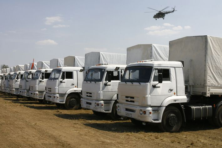 """Trucks from a Russian humanitarian convoy are parked on a field outside the town of Kamensk-Shakhtinsky in the Rostov region, some 30kms from the Russian-Ukrainian border, Russia, on August 14, 2014. A massive Russian """"humanitarian"""" convoy closed in on Ukraine's border today despite doubts over whether the trucks would be allowed across, and as deadly fighting rocked rebel-held strongholds. The nearly 300 vehicles headed towards southeastern Ukraine, even as intense shelling there in the insurgent bastions of Donetsk and Lugansk -- where the trucks appear headed -- sharply increased the death toll from fighting."""