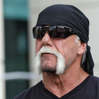 Reality TV star and former pro wrestler Hulk Hogan, whose real name is Terry Bollea, looks on as his attorney speaks during a news conference Monday, Oct. 15, 2012 at the United States Courthouse in Tampa, Fla. Hogan says he was secretly taped six years ago having sex with the ex-wife of DJ Bubba