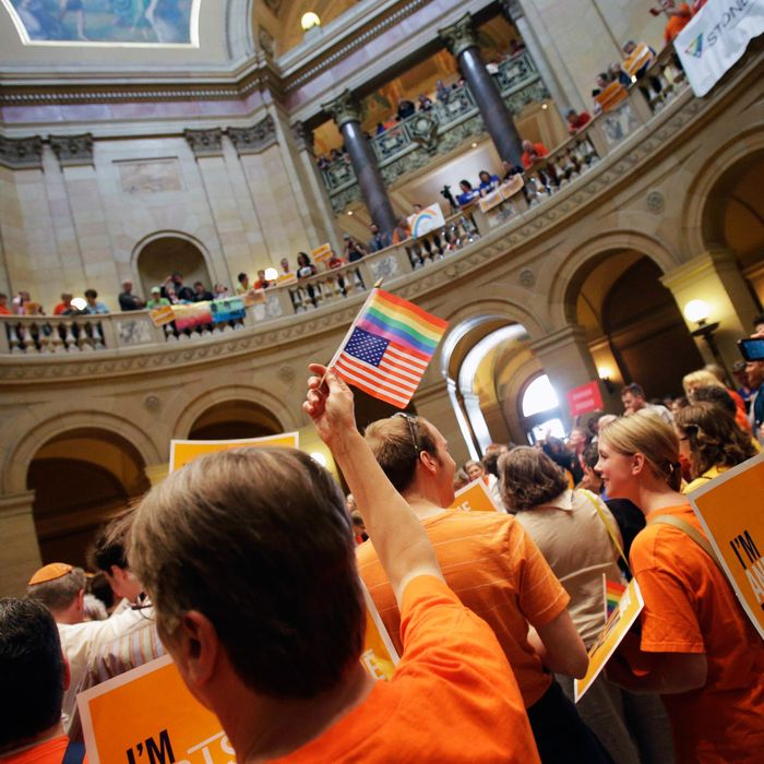 A gay marriage supporter waves the U.S. flag and a rainbow flag as supporters and opponents of Minnesota's gay marriage bill gather in the State Capitol rotunda in St. Paul as the Senate prepared to take up the issue Monday, May 13, 2013 in St. Paul, Minn. The bill passed the Minnesota House last week.
