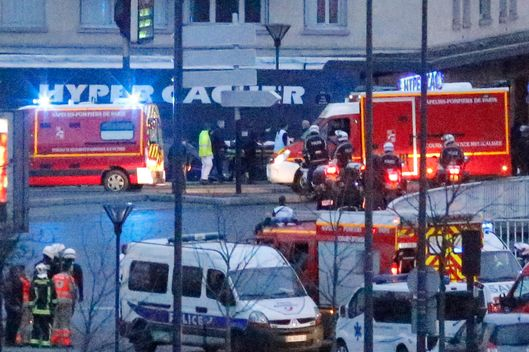 Rescue workers enter after police forces stormed the kosher store where a gunman held several hostages, in Paris, Friday Jan. 9, 2015.