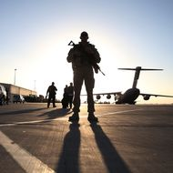 A soldier stands guard near a C17 military aircraft sitting on the tarmac, on December 8, 2013 in Kandahar. US Defense Secretary Chuck Hagel told American troops on Sunday that he supports a NATO force in Afghanistan after 2014, as Washington and President Hamid Karzai wrangle over a stalled security pact. AFP PHOTO POOL MARK WILSON