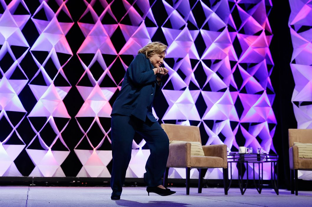 Former Secretary of State Hillary Clinton ducks after a woman threw an object toward her while she was delivering remarks at the Institute of Scrap Recycling Industries conference on April 10, 2014 in Las Vegas, Nevada. Clinton is continuing on a speaking tour this week with the stop at the recycling industry trade conference.