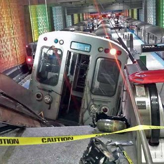 A Chicago Transit Authority train car rests on an escalator at the O'Hare Airport station after it derailed early Monday, March 24, 2014, in Chicago. More than 30 people were injured after the train