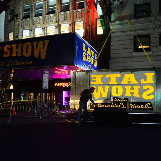 Workers remove the 'Late Show with David Letterman' sign on the Ed Sullivan Theater marquee in New York City, NY