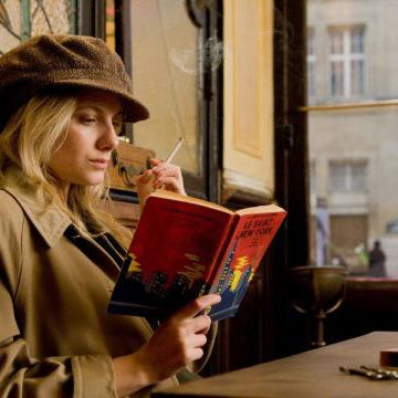 Melanie Laurent, reading a book and smoking a cigarette in a Parisian cafe