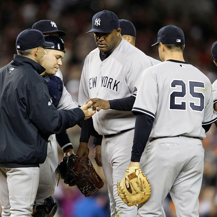 New York Yankee manager Joe Girardi #28 makes a pitching change removing C.C. Sabathia #52 in the sixth inning.