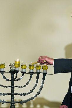David Ben-Gurion's grandson Yariv Ben-Eliezer lights the Menorah during the Hanukkah reception at White House in Washington, DC, December 15, 2008.     AFP PHOTO/Jim WATSON (Photo credit should read JIM WATSON/AFP/Getty Images)