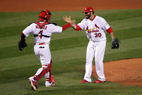 ST LOUIS, MO - OCTOBER 19:  Jason Motte #30 and Yadier Molina #4 of the St. Louis Cardinals celebrate after defeating the Texas Rangers 3-2 during Game One of the MLB World Series at Busch Stadium on October 19, 2011 in St Louis, Missouri.  (Photo by Doug Pensinger/Getty Images)