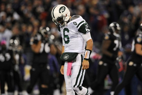 Quarterback Mark Sanchez #6 of the New York Jets walks to the sideline after being sacked by nose tackle Haloti Ngata #92 of the Baltimore Ravens.