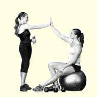 Caucasian women high fiving in gym .