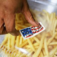 """WASHINGTON - MARCH 12:  A cashier put a """"freedom sticker"""" on top of a box of """"Freedom Fries"""" at a cafeteria in the U.S. Capitol building on Capitol Hill March 12, 2003 in Washington, DC. With the French opposition of U.S. President Bush's policy on Iraq, the House Administration Committee ordered to change the names of French Fries and French Toast to """"Freedom Fries"""" and """"Freedom Toast"""" in all the cafeterias of the House of Representatives.  (Photo by Alex Wong/Getty Images)"""