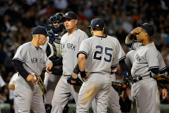 CHICAGO, IL - AUGUST 20:  Joe Girardi #28 of the New York Yankees (L) takes out starting pitcher Freddy Garcia #36 (C) during the fifth inning against the Chicago White Sox at U.S. Cellular Field on August 20, 2012 in Chicago, Illinois.  (Photo by Brian Kersey/Getty Images)