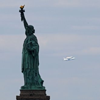 NEW YORK, NY - APRIL 27: Space shuttle Enterprise, mounted atop a 747 shuttle carrier aircraft, flies past the Statue of Liberty prior to landing at John F. Kennedy International Airport on April 27, 2012 in New York City. Enterprise, which was flown from Washington, DC, will eventually be put on permanent display at the Intrepid Sea, Air and Space Museum. (Photo by Michael Heiman/Getty Images)