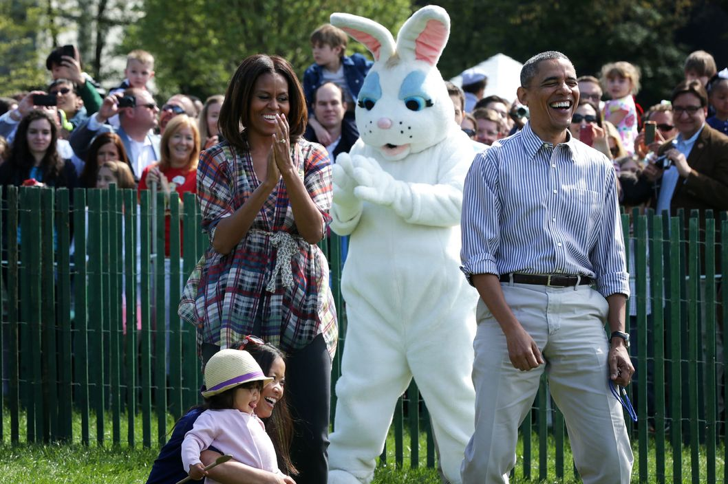 U.S. President Barack Obama (R) and first lady Michelle Obama (L) watch children participate in the annual White House Easter Egg Roll on the South Lawn April 21, 2014 in Washington, DC. President Obama and the first lady hosted thousands of children for the annual White House event dating back to 1876 that features live music, sports courts, cooking stations, storytelling, as well as the Easter egg roll this year.