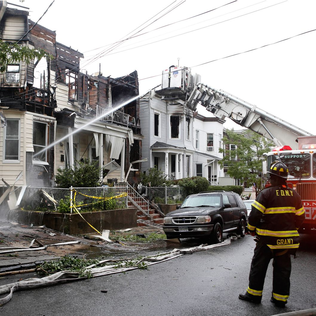 A firefighter, right, watches as another sprays water on 205 Chestnut Avenue in the Staten Island borough of New York, Thursday, June 5, 2014, where 34 people were injured after fire tore through three townhouses on the street early Thursday. Two children were tossed out of a smoke-filled second-story window into the arms of neighbors below, according to authorities and witnesses.  (AP Photo/Kathy Willens)