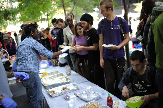 "Members of Occupy Wall Street line up for their free breakfast served by volounteers after spending the night on Zuccotti Park near Wall Street in New York, October 11, 2011. Protesters from the Occupy Wall Street movement scheduled a ""Millionaires March"" taking their march in front of the homes of some of New York City's wealthiest residents in Manhattan Upper East Side. AFP PHOTO/Emmanuel Dunand (Photo credit should read EMMANUEL DUNAND/AFP/Getty Images)"