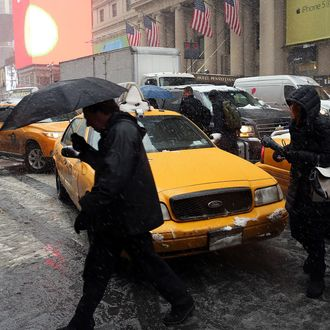 People walk across a street inbetween taxis during a snowstorm in Manhattan on February 3, 2014 in New York City. The metro area is expecting 5 to 8 inches of snow by the evening, making for a treacherous rush hour and delaying many flights to airports.