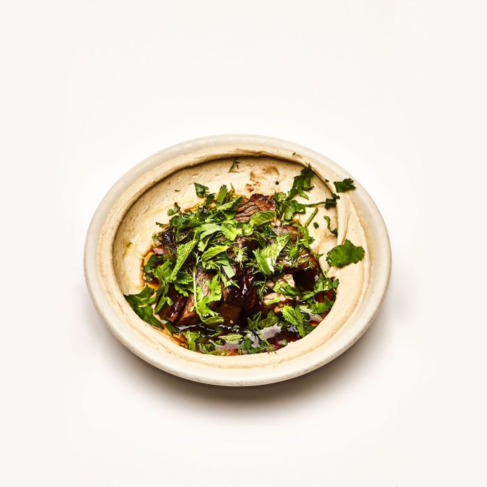 Hummus with braised lamb neck, dried lime, and herbs.