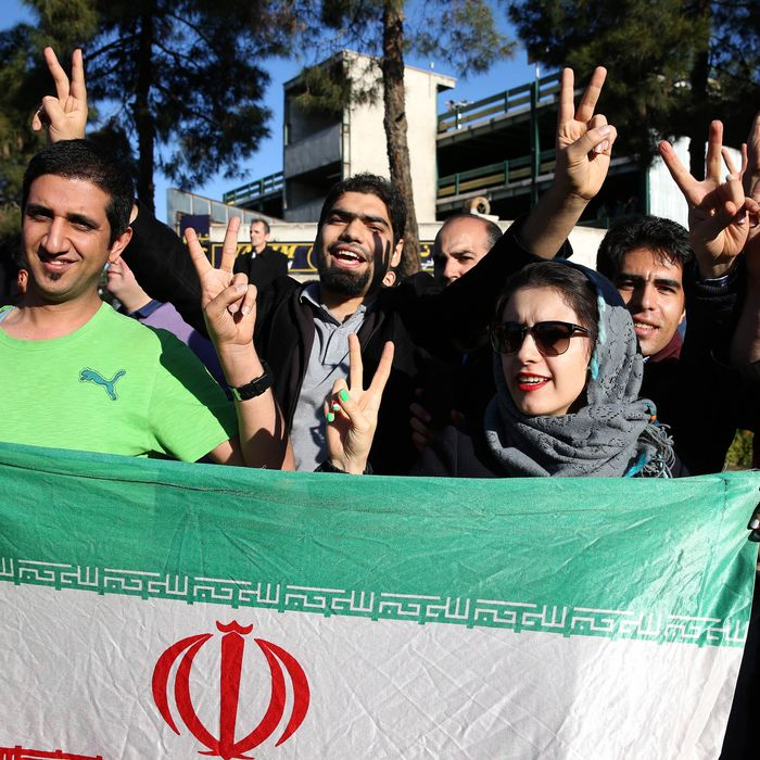 Iranians flash the victory sign as they hold their country's flag while waiting for arrival of Foreign Minister Mohammad Javad Zarif from Lausanne, Switzerland, at the Mehrabad airport in Tehran, Iran, Friday, April 3, 2015. Iran and six world powers reached a preliminary nuclear agreement Thursday outlining commitments by both sides as they work for a comprehensive deal aiming at curbing nuclear activities Tehran could use to make weapons and providing sanctions relief for Iran. (AP Photo/Ebrahim Noroozi)