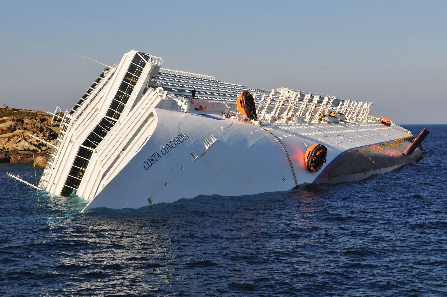 GIGLIO PORTO, ITALY - JANUARY 14:  The cruise ship Costa Concordia lies stricken off the shore of the island of Giglio, on January 14, 2012 in Giglio Porto, Italy. More than four thousand people were on board when the ship hit a sandbank. At least 3 people have been confirmed dead and another 50 are unaccounted for. (Photo by Laura Lezza/Getty Images)