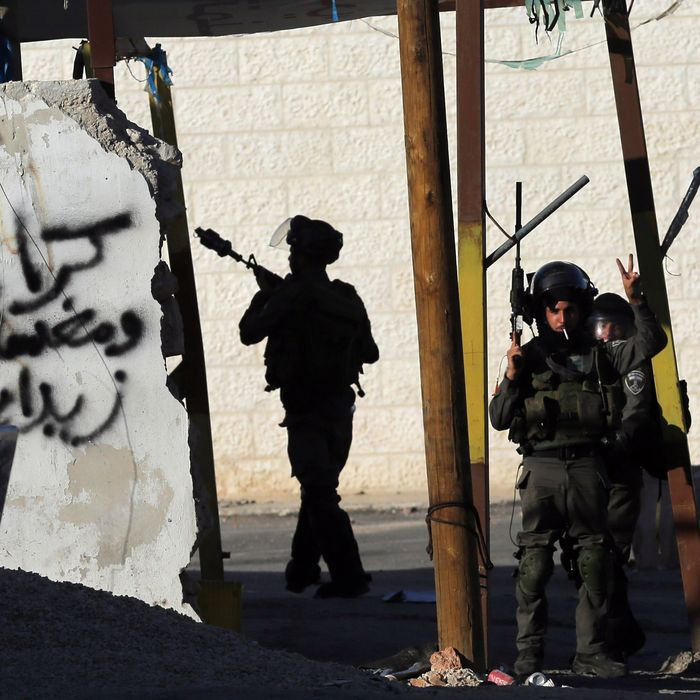 A member of the Israeli security forces flashes the sign for victory during clashes with Palestinian youths from the Jalazoun refugee camp at the entrance of the Jewish West Bank settlement Beit El, north of Ramallah, following a march by Palestinian demonstrators against Israeli restrictions on the Al-Aqsa mosque and against Jewish settlements in the West Bank on October 24, 2014.