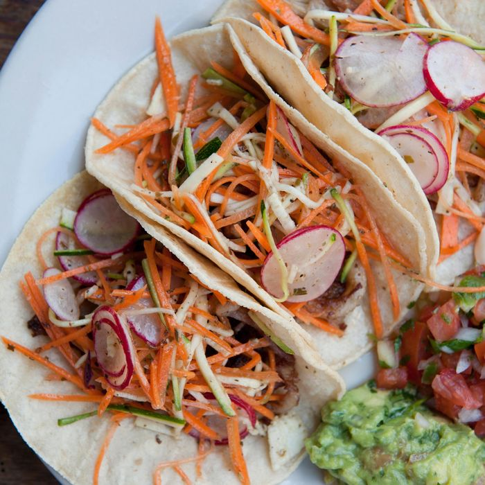 Pork belly tacos with radishes, carrots, zucchini salad, and oregano mojo.