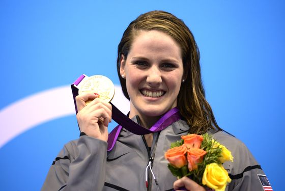 US swimmer Missy Franklin poses on the podium with the gold medal after winning the women's 100m backstroke swimming event at the London 2012 Olympic Games in the Aquatics Centre at the Olympic Park in London on July 30, 2012.  AFP PHOTO / LEON NEAL        (Photo credit should read LEON NEAL/AFP/GettyImages)