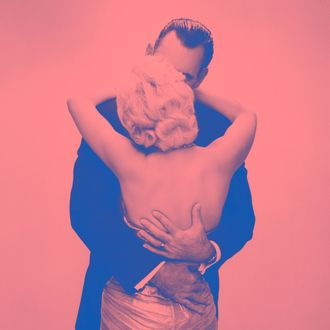 05 Jul 1956 --- 1950s 1960s kissing couple blond woman backless satin evening dress man embracing from behind --- Image by ? Ewing Galloway/ClassicStock/Corbis