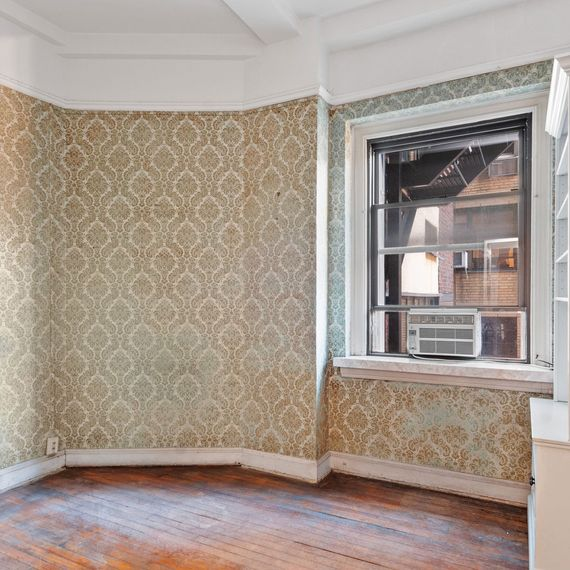 Room with gold patterned wallpaper and wood floors.