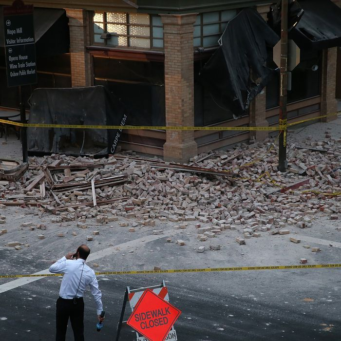 NAPA, CA - AUGUST 24: A reporter surveys the scene of a building collapse following a reported 6.0 earthquake on August 24, 2014 in Napa, California. A 6.0 earthquake rocked the San Francisco Bay Area shortly after 3:00 am on Sunday morning causing damage to buildings and sending at least 70 people to a hospital with non-life threatening injuries. (Photo by Justin Sullivan/Getty Images)