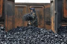File photo of a worker unloading coal at a storage site along a railway station in Shenyang