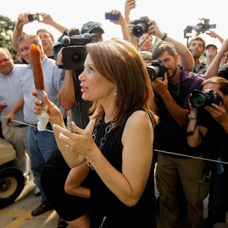 DES MOINES, IA - AUGUST 12: Republican presidential candidate Rep. Michele Bachmann (R-MN) shows off her foot-long corn dog as photographers take her picture at the Iowa State Fair August 12, 2011 in Des Moines, Iowa. Unlike any of the other GOP hopefuls at the fair, Bachmann arrived 30 minutes late for her scheduled speech and spoke for less than three minutes of her alloted 20 minutes then left on a golf cart guarded by state troopers. All of the Republican presidential hopefuls are visiting the fair ahead of Saturday's Iowa Straw Poll to greet voters and engage in traditional Iowa campaigning rituals. (Photo by Chip Somodevilla/Getty Images)