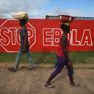 MONROVIA, LIBERIA - OCTOBER 02: People pass an Ebola awareness mural on October 2, 2014 in Monrovia, Liberia. More than 3,200 people have died in West Africa due to the epidemic. (Photo by John Moore/Getty Images)