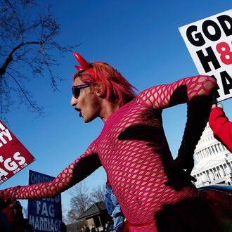 New York based drag performer Queen dances during a rally while surrounded by protesters from the conservative Westboro Baptist Church in front of the U.S. Supreme Court on March 26, 2013 in Washington, DC. The Supreme Court is hearing arguments March 26, in California's proposition 8, the controversial ballot initiative that defines marriage only between a man and a woman.