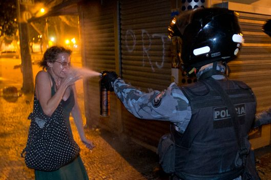 A military police peper sprays a protester during a demonstration in Rio de Janeiro, Brazil, Monday, June 17, 2013. Protesters massed in at least seven Brazilian cities Monday for another round of demonstrations voicing disgruntlement about life in the country, raising questions about security during big events like the current Confederations Cup and a papal visit next month. ((AP Photo/Victor R. Caivano)