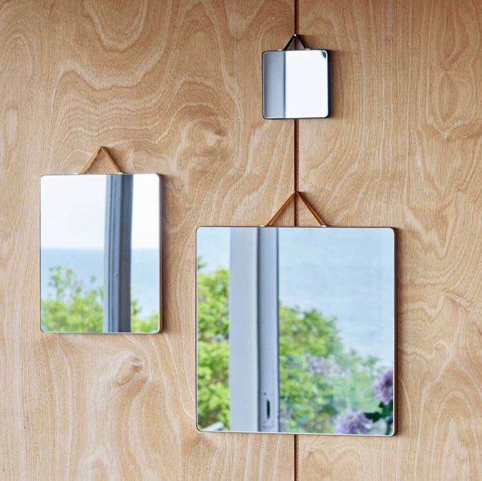 set of mirrors reflecting flowers set against a wooden backdrop - strategist best decorative mirrors