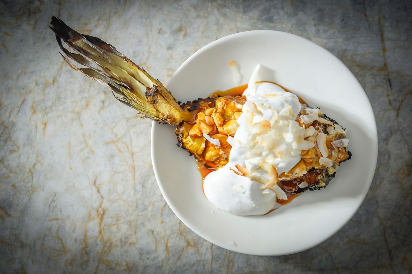 Pastry chef Italivi Reboreda's tandoor-roasted pineapple with tamarind glaze, vegan whipped cream, and macadamia nuts.