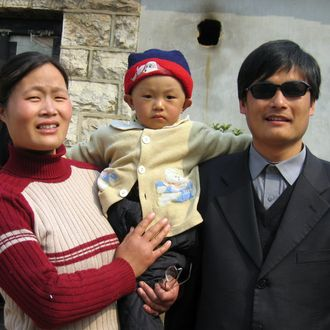 A picture dated March 28, 2005 shows blind activist Chen Guangcheng (R) with his wife and son Chen Kerui outside the home in Dondshigu village, northeast China's Shandong province. Chen, who gained worldwide fame for exposing abuses in China's