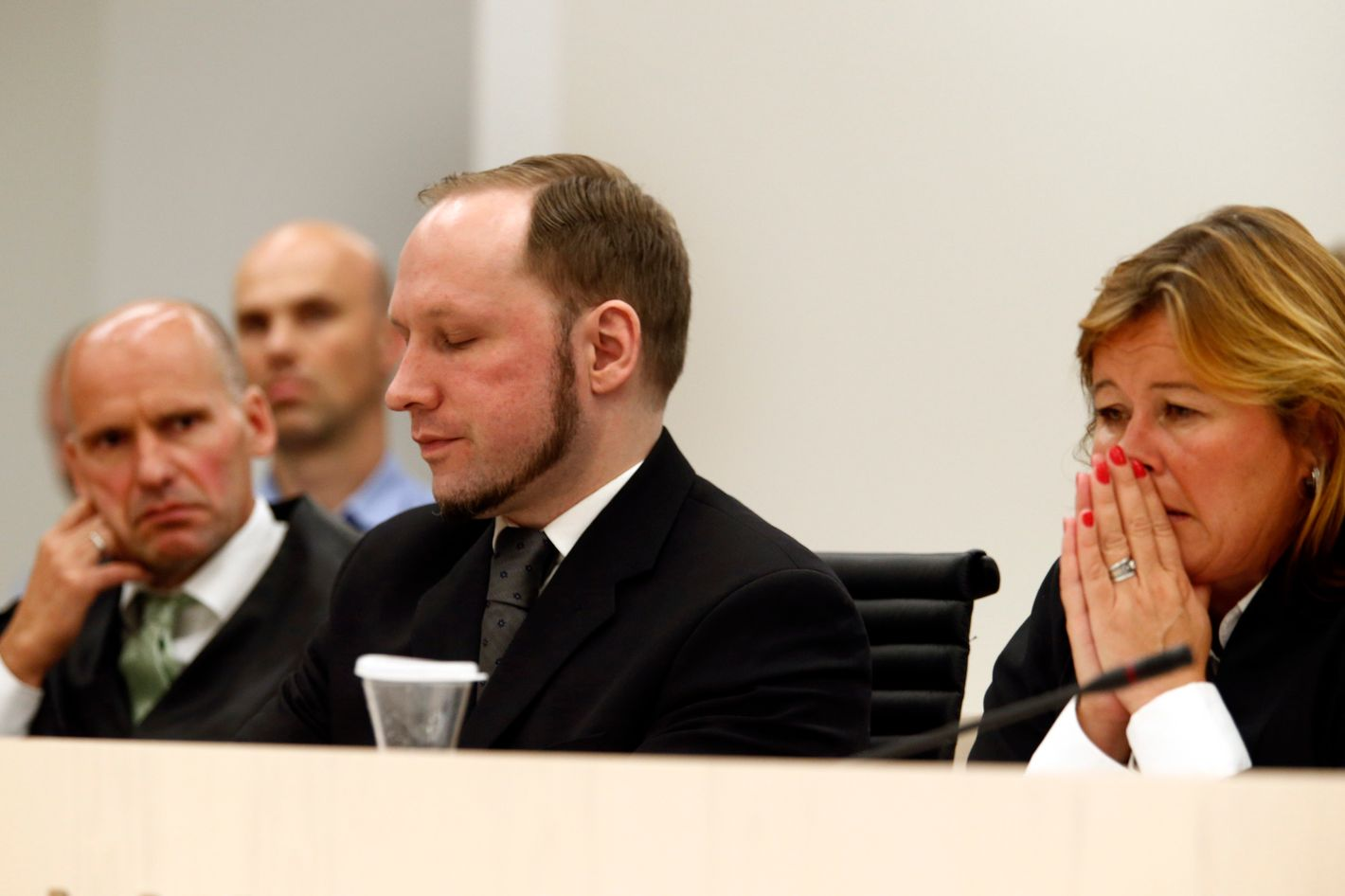 "Defender Geir Lippestad (left) and defender Vibeke Hein Baera sit together with terror accused Anders Behring Breivik when Oslo Court passes judgment against him in Oslo Courthouseon August 24, 2012. The court on Friday found Anders Behring Breivik guilty of ""acts of terror"" and sentenced him to 21 years in prison for his killing spree last year that left 77 people dead."