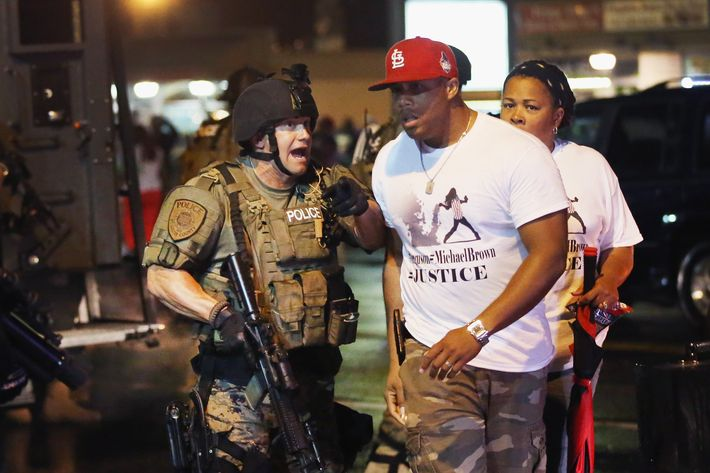 FERGUSON, MO - AUGUST 15: Police confront demonstrators during a protest over the shooting of Michael Williams on August 15, 2014 in Ferguson, Missouri. County police shot pepper spray, smoke, gas and flash grenades at protestors before retreating. Several businesses were looted as county police watched from their armored personnel carriers (APC) parked nearby. Violent outbreaks have taken place in Ferguson since the shooting death of Brown by a Ferguson police officer on August 9. (Photo by Scott Olson/Getty Images)