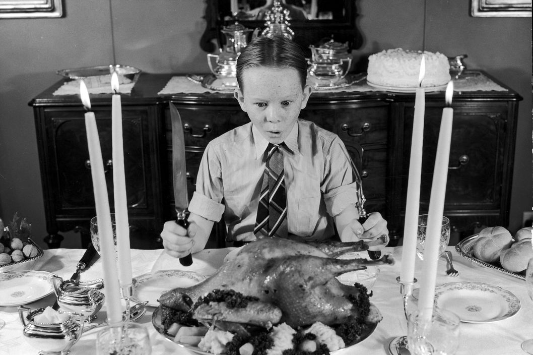 A freckle-faced boy sitting at the Thanksgiving dinner table gasps in awe at the roasted turkey, as he clutches carving utensils.