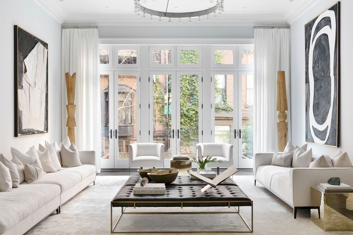 Apartment With White Walls, White Couches, Leather Ottoman, And Coffee  Table Book