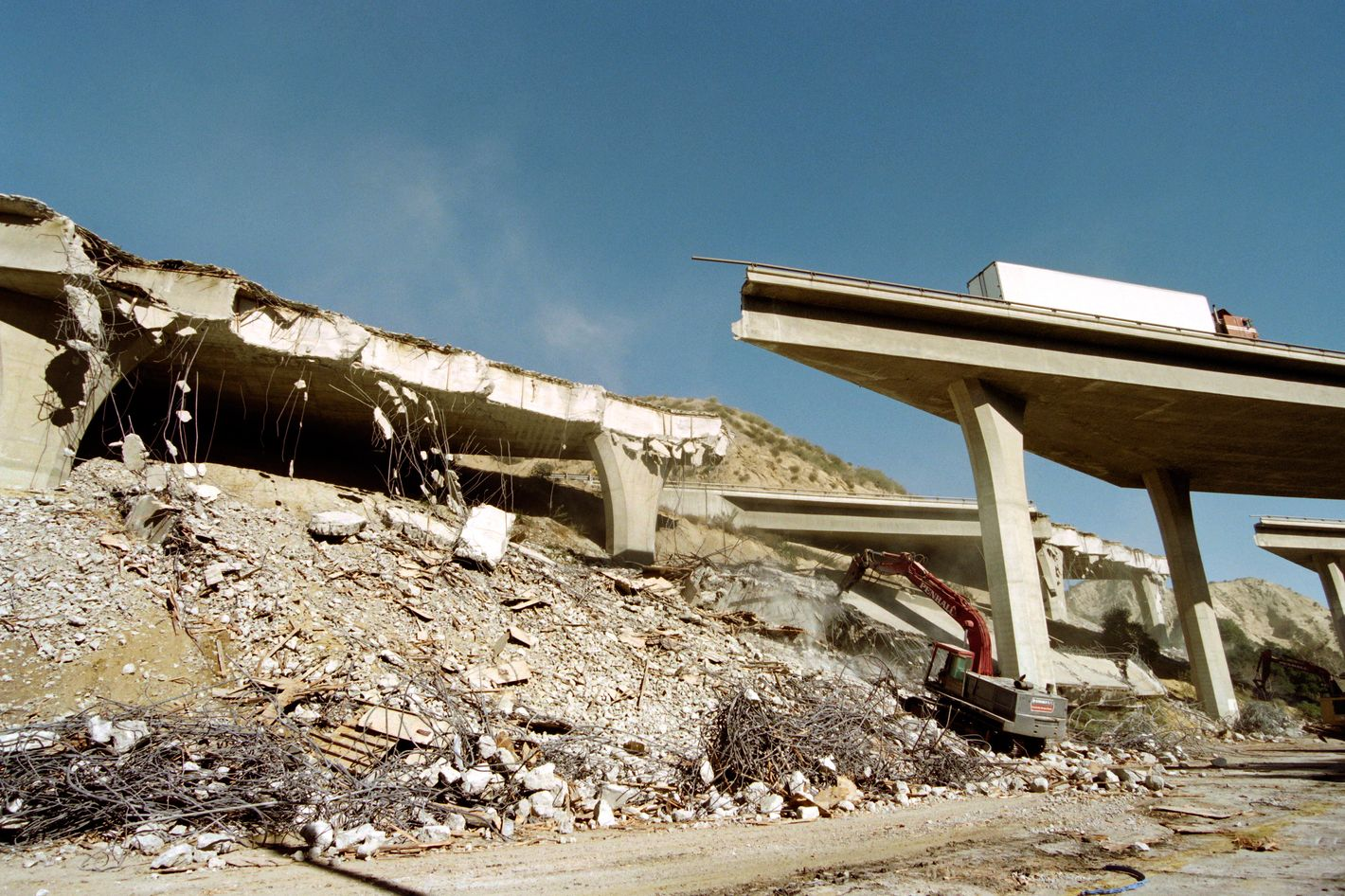 Heavy equipment prepares for moving portions of Interstate 5 as an abandoned truck rests on the dmaged structure on January 18, 1994.  The highway collapsed January 17 when an earthquake hit the region, causing 7 billion USD in damage in the area.      AFP PHOTO TIM CLARY        (Photo credit should read TIM CLARY/AFP/GettyImages)