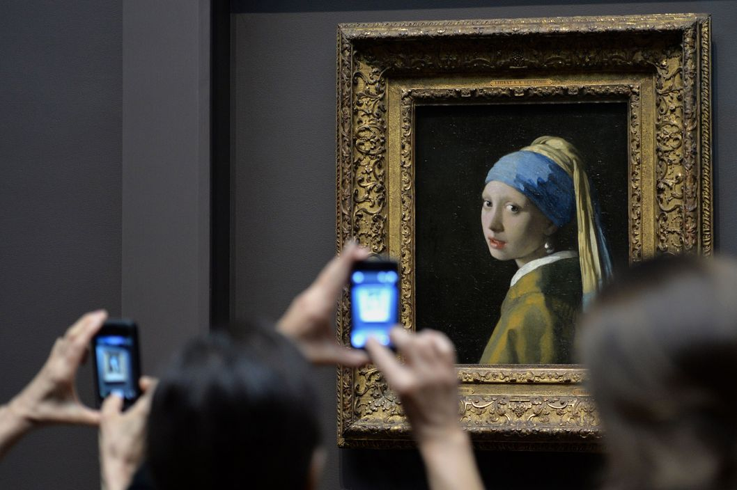 "People view ""Girl with a Pearl Earring (c. 1665)"" by Johannes Vermeer in the exhibition ""Vermeer, Rembrandt, and Hals: Masterpieces of Dutch Painting from the Mauritshuis"" October 21, 2013 at the Frick Collection in New York. The special exhibition is the final US venue of a global tour of paintings from the Royal Picture Gallery Mauritshuis in The Hague, the Netherlands and runs from October 22, 2013 to January 19, 2014."