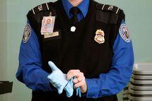 A TSA agent dons rubber gloves at Washington Reagan National Airport
