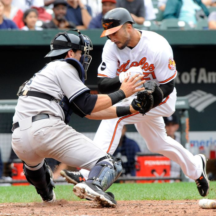 BALTIMORE, MD- SEPTEMBER 8: Nick Markakis #21 of the Baltimore Orioles collides with catcher Francisco Cervelli of the New York Yankees while trying unsuccessfully to score in the 7th inning of a game against the New York Yankees at Oriole Park at Camden Yards on September 8, 2011 in Baltimore, Maryland. The Orioles beat the Yankees 5-4 in ten innings. (Photo by Steve Ruark/Getty Images)