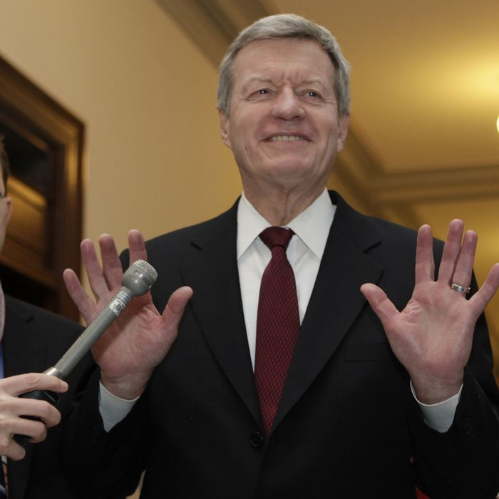 Super committee member Senator Max Baucus (D-MT) gestures to the media as he arrives at the meeting between Republican and Democratic members of the