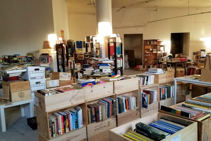 Books in crates and bookshelves and tables spread across a lobby.